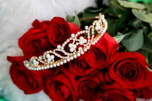 Pearl and rhinestone tiara laying across a dozen red roses