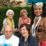Residents posing with one of our luau dancers.