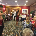 Luau performers dancing for the residents to set the mood for the event during social hour.