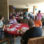 Residents socializing with each other and enjoying the food, music and weather during the Friday BBQ.