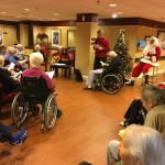 Residents, volunteers and associates enjoying our holiday community sing-along with Santa visiting.
