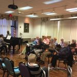 Our musical director, Gena Photiadis on the piano accompanying our resident chorus together with a bass and sax players.