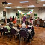 Residents, associates and family members learning how to dance pearly shells.
