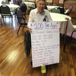 Our happy celebrant holding a big card highlighting events during his life.