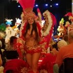 Beautiful performers on elaborate costumes walking down the aisle to greet the audience.