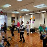 Residents and associates line dancing to Macarena and Cupid Shuffle