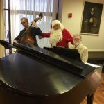 Santa singing along with the East Coast performers during Mix and Mingle