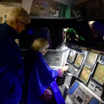 Barbara and Pat studying the control area in one of the space shuttle's exhibit