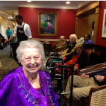 Resident with a beautiful smile and dressed in a bright purple outfit to celebrate the festivities