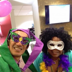 Staff wearing the Mardi Gras outfit participating in the fun event